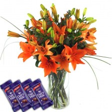 Orange Lilies In A Vase With Chocolates